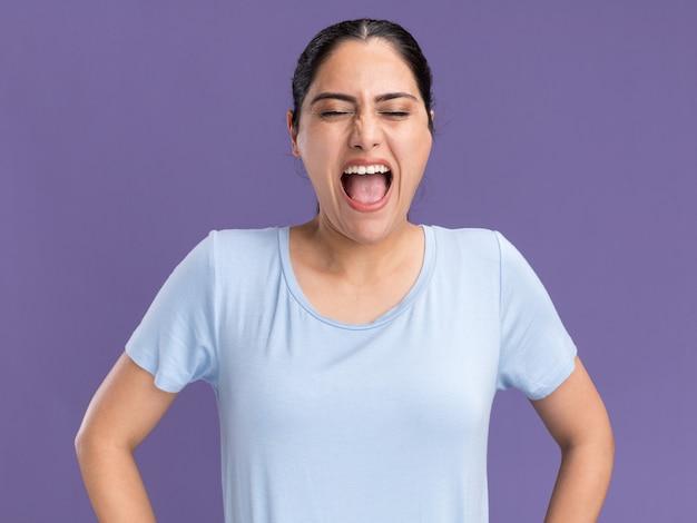 Geërgerd jong donkerbruin kaukasisch meisje dat tegen iemand op paars schreeuwt