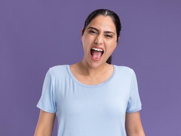 Geërgerd jong donkerbruin kaukasisch meisje dat tegen iemand schreeuwt die op paarse muur met exemplaarruimte wordt geïsoleerd