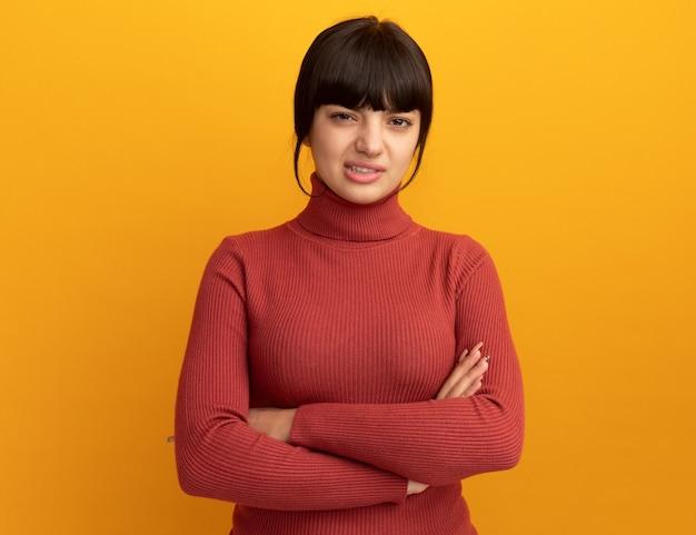 Geërgerd jong donkerbruin kaukasisch meisje dat zich met gekruiste wapens op sinaasappel bevindt