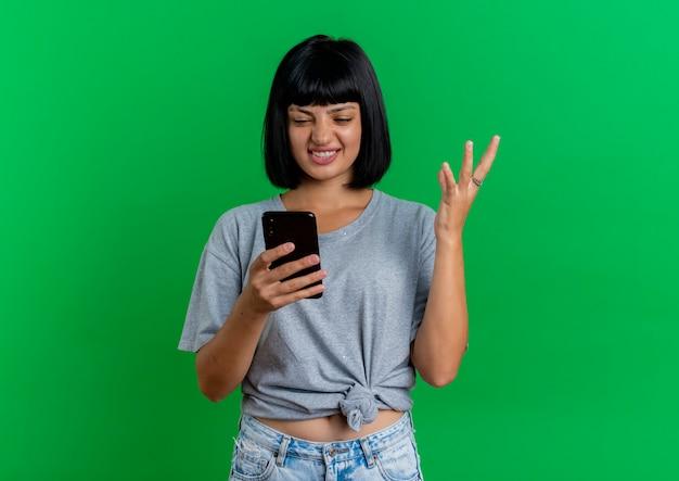 Geërgerd jong donkerbruin kaukasisch meisje heft hand op en bekijkt telefoon die op groene achtergrond met exemplaarruimte wordt geïsoleerd