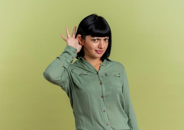 Geërgerd jong donkerbruin kaukasisch meisje houdt hand achter oor probeert te horen geïsoleerd op olijfgroene achtergrond met exemplaarruimte