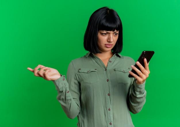 Geërgerd jong donkerbruin kaukasisch meisje kijkt naar telefoon en houdt hand open geïsoleerd op groene achtergrond met exemplaarruimte