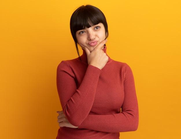 Geërgerd jong donkerbruin kaukasisch meisje legt hand op kin en kijkt naar kant die op oranje muur met exemplaarruimte wordt geïsoleerd