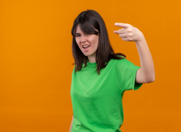 Geërgerd jong kaukasisch meisje in groen overhemd wijst vooruit en bekijkt camera op geïsoleerde oranje achtergrond met exemplaarruimte