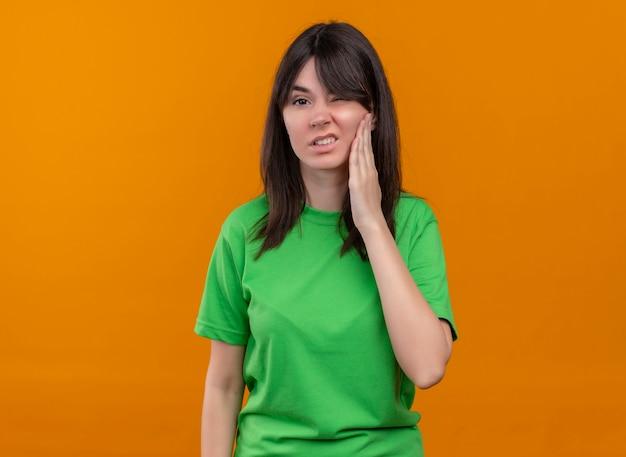 Geërgerd jong kaukasisch meisje in groen shirt houdt gezicht en kijkt naar camera op geïsoleerde oranje achtergrond