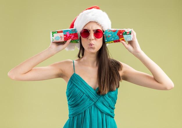 Geërgerd jong kaukasisch meisje in zonnebril met kerstmuts die oren sluit met papieren bekers geïsoleerd op olijfgroene muur met kopieerruimte