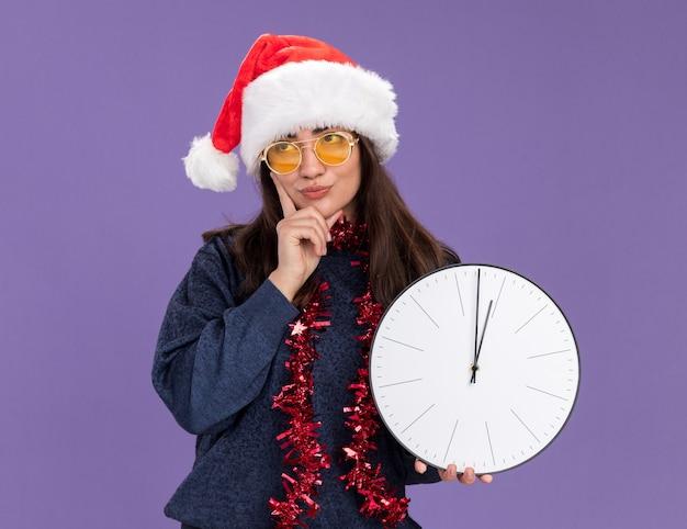 Geërgerd jong kaukasisch meisje in zonnebril met kerstmuts en slinger om nek houdt klok vast en legt hand op kin rollende ogen geïsoleerd op paarse muur met kopieerruimte