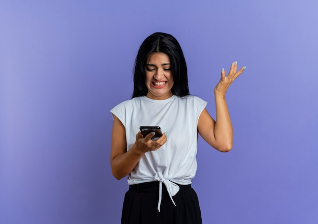 Geërgerd jong kaukasisch meisje kijkt naar telefoon en steekt hand op