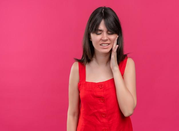 Geërgerd jong kaukasisch meisje legt hand op gezicht en kijkt neer op geïsoleerde roze achtergrond met kopie ruimte