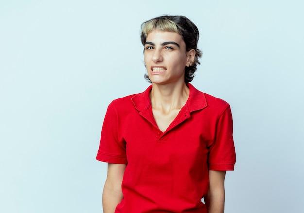 Geërgerd jong kaukasisch meisje met pixiekapsel die camera bekijken die op witte achtergrond met exemplaarruimte wordt geïsoleerd