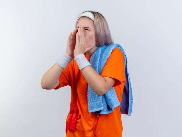 Geërgerd jong kaukasisch sportief meisje met beugels en met touwtjespringen om de nek dragen hoofdband polsbandjes houden handdoek op schouder iemand bellen kijken kant op witte muur