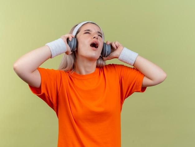 Geërgerd jong kaukasisch sportief meisje met beugels met hoofdband en polsbandjes houdt een koptelefoon vast