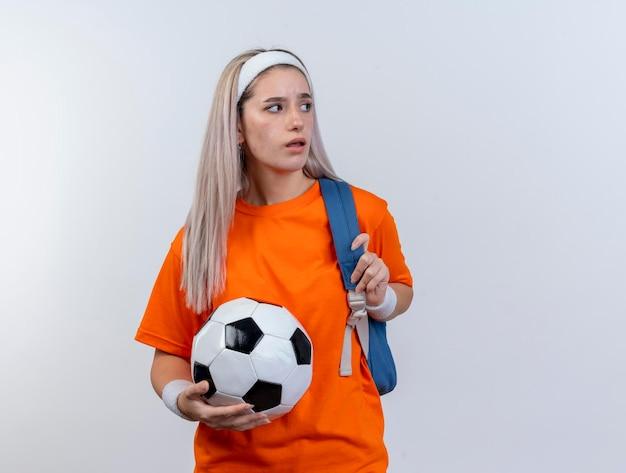 Geërgerd jong kaukasisch sportief meisje met steunen die rugzakhoofdband en polsbandjes dragen