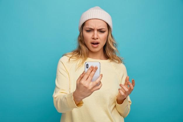 Geërgerd jong meisje dragen winter hoed houden en kijken naar mobiele telefoon houden hand in de lucht