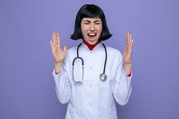 Geërgerd jong mooi kaukasisch meisje in doktersuniform met stethoscoop staat met gesloten ogen die handen open houden