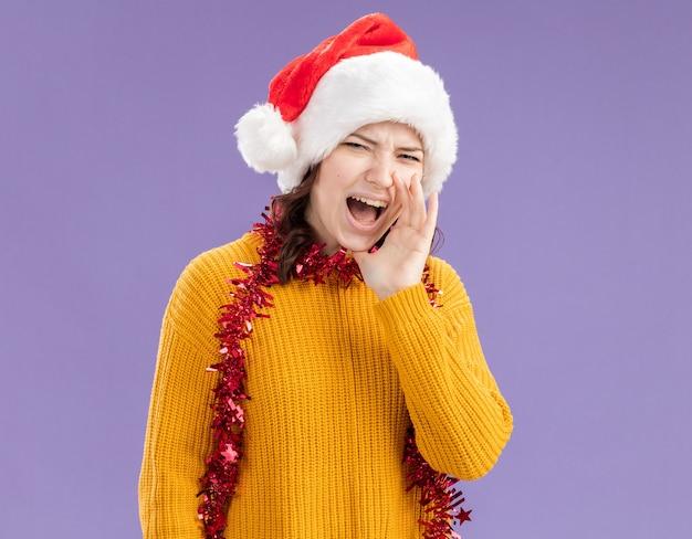 Geërgerd jong slavisch meisje met kerstmuts en met slinger om nek houdt hand dicht bij mond schreeuwen tegen iemand kijken naar camera geïsoleerd op paarse achtergrond met kopie ruimte