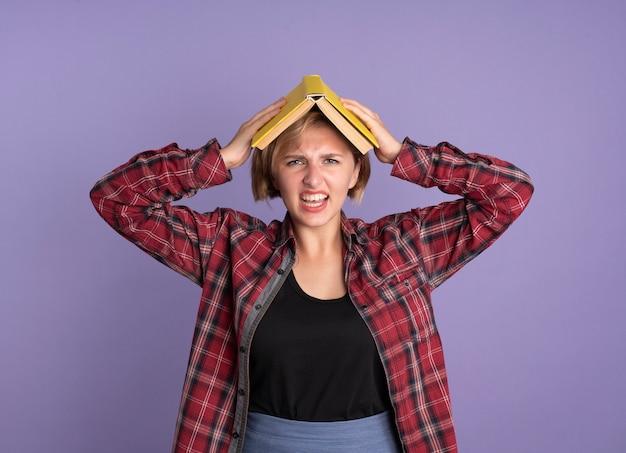 Geërgerd jong slavisch studentenmeisje houdt boek boven haar hoofd