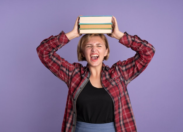 Geërgerd jong slavisch studentenmeisje houdt boeken boven haar hoofd