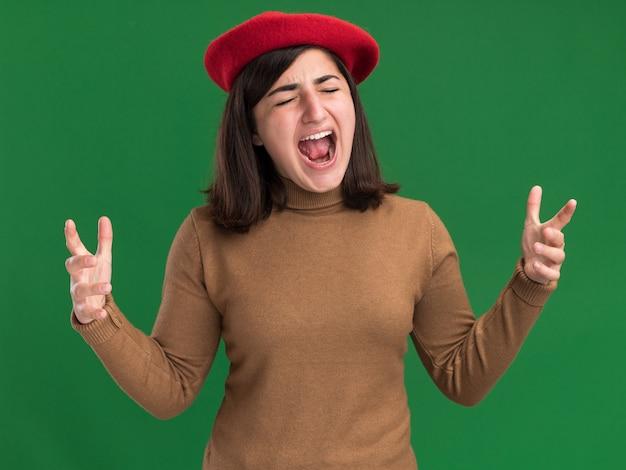 Geërgerd jong vrij kaukasisch meisje met baret hoed staat met gesloten ogen schreeuwen tegen iemand op groen