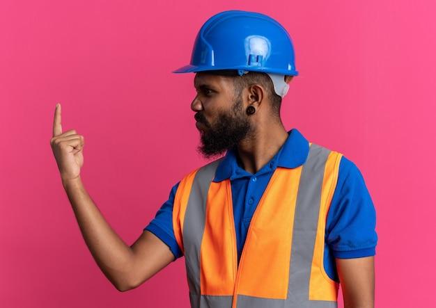 Geërgerd jonge afro-amerikaanse bouwer man in uniform met veiligheidshelm kijken naar zijn vinger geïsoleerd op roze achtergrond met kopie ruimte
