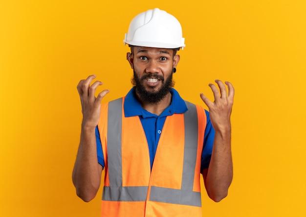 Geërgerd jonge afro-amerikaanse bouwer man in uniform met veiligheidshelm staande met opgeheven handen geïsoleerd op oranje achtergrond met kopie ruimte