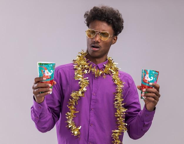 Geërgerd jonge afro-amerikaanse man met bril met klatergoud slinger rond de nek met plastic kerstbekers kijken naar een van hen geïsoleerd op witte achtergrond