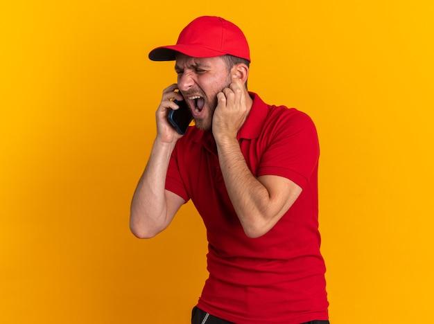 Geërgerd jonge blanke bezorger in rood uniform en pet staande in profielweergave praten over telefoon zetten vinger op oor schreeuwen met gesloten ogen geïsoleerd op oranje muur met kopie ruimte