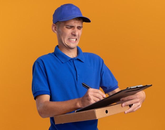 Geërgerd jonge blonde bezorger schrijft op klembord met pen die op pizzadoos op sinaasappel houdt