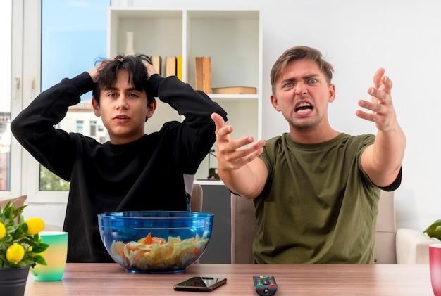 Geërgerd jonge blonde knappe man houdt handen uit wijzend op camera zittend aan tafel met geschokt jonge brunette knappe jongen hoofd met twee handen in woonkamer houden