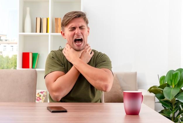 Geërgerd jonge blonde knappe man zit aan tafel met telefoon en kopje zichzelf verstikking met twee handen in de woonkamer