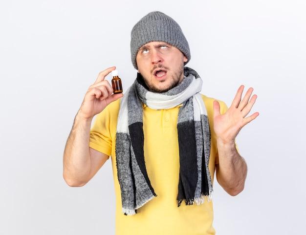 Geërgerd jonge blonde zieke man met muts en sjaal staat met opgeheven hand en houdt geneeskunde in glazen fles geïsoleerd op een witte muur