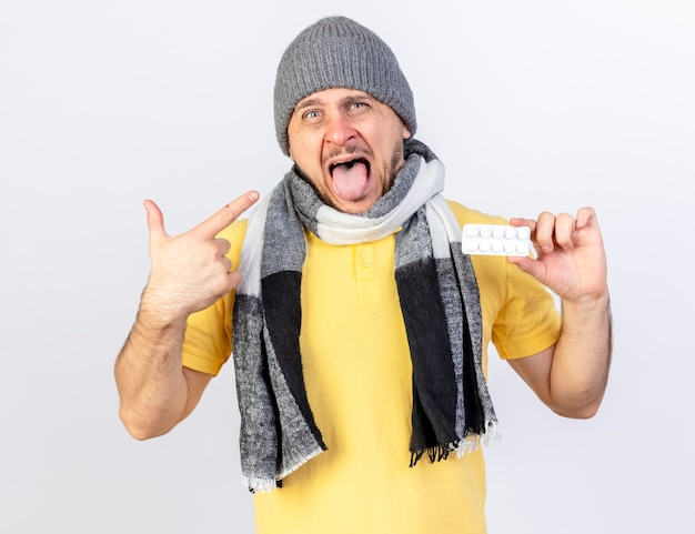 Geërgerd jonge blonde zieke man met winter hoed en sjaal houdt pakje medische pillen en punten aan de zijkant geïsoleerd op een witte muur