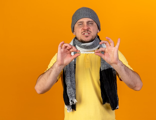 Geërgerd jonge blonde zieke slavische man met winter hoed en sjaal houdt thermometer