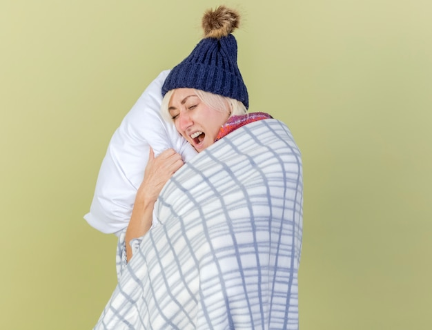 Geërgerd jonge blonde zieke slavische vrouw met muts en sjaal gewikkeld in geruite knuffels kussen geïsoleerd op olijfgroene muur met kopie ruimte