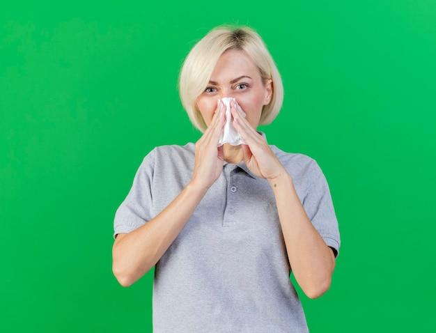 Geërgerd jonge blonde zieke slavische vrouw veegt neus met weefsel af dat op groene muur met exemplaarruimte wordt geïsoleerd