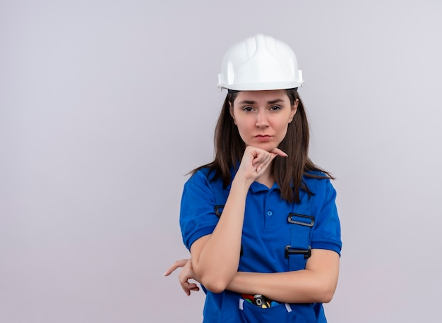 Geërgerd jonge bouwer meisje met witte veiligheidshelm en blauw uniform legt hand op kin en kijkt naar camera op geïsoleerde witte achtergrond met kopie ruimte