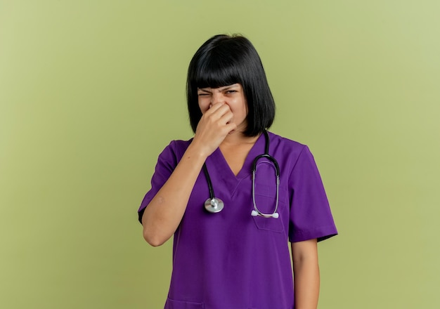 Geërgerd jonge brunette vrouwelijke arts in uniform met stethoscoop houdt neus kijken camera geïsoleerd op olijfgroene achtergrond met kopie ruimte