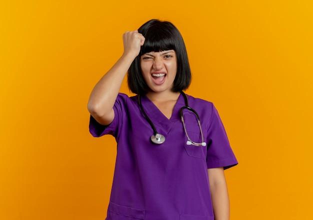 Geërgerd jonge brunette vrouwelijke arts in uniform met stethoscoop zet vuist op hoofd geïsoleerd op een oranje achtergrond met kopie ruimte