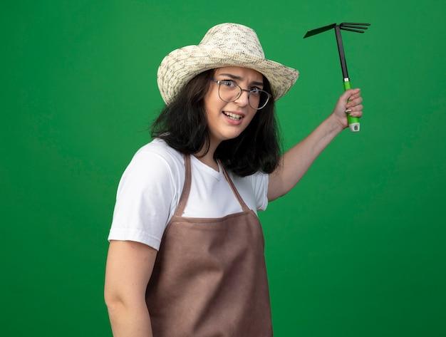 Geërgerd jonge brunette vrouwelijke tuinman in optische bril en uniform dragen tuinieren hoed houdt schoffelhark geïsoleerd op groene muur