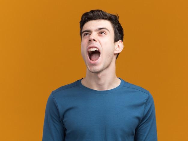 Geërgerd jonge donkerbruine kaukasische jongen die tegen iemand schreeuwt die omhoog op sinaasappel kijkt