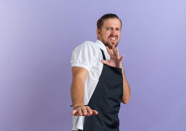 Geërgerd jonge knappe kapper dragen uniform strekken hand gebaren niet geïsoleerd op paars met kopie ruimte
