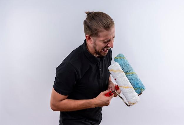 Geërgerd jonge knappe man in zwart poloshirt schreeuwen bedrijf verfrollen permanent op witte achtergrond