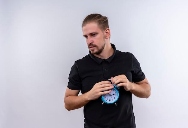 Geërgerd jonge knappe man in zwarte polo shirt bedrijf wekker opzij kijken met ernstig gezicht staande op witte achtergrond
