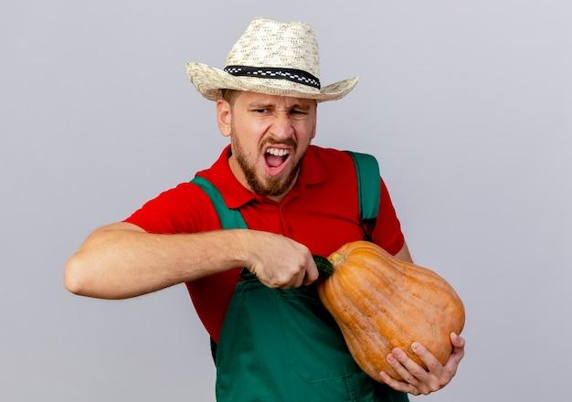 Geërgerd jonge knappe slavische tuinman in uniform en hoed aanraken butternut pompoen met komkommer op zoek geïsoleerd