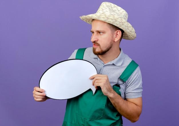 Geërgerd jonge knappe slavische tuinman in uniform en hoed met praatjebel kijken kant geïsoleerd op paarse muur
