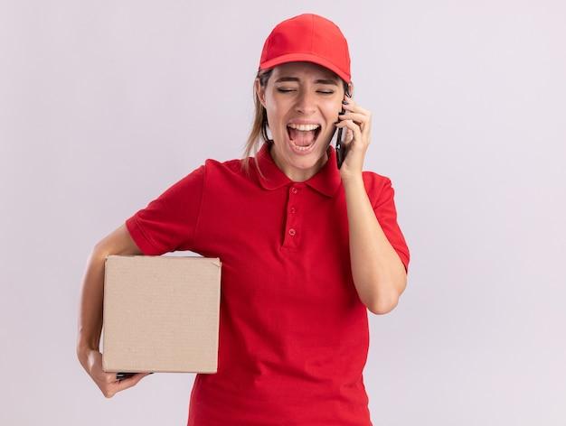 Geërgerd jonge mooie bezorgvrouw in uniform houdt kartonnen doos en schreeuwt tegen iemand op de telefoon geïsoleerd op een witte muur