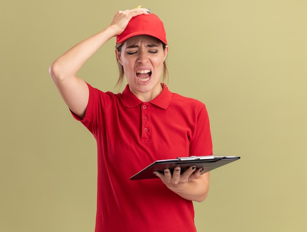 Geërgerd jonge mooie bezorgvrouw in uniform legt hand op hoofd met potlood en kijkt naar klembord geïsoleerd op olijfgroene muur