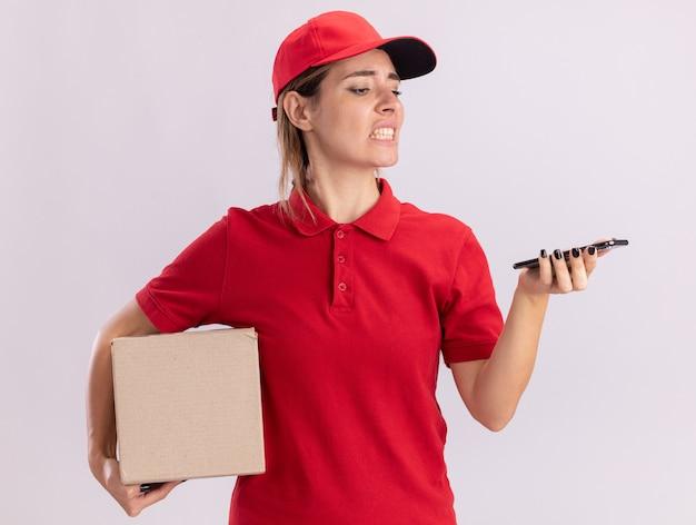 Geërgerd jonge mooie levering meisje in uniform houdt kartonnen doos en kijkt naar telefoon op wit