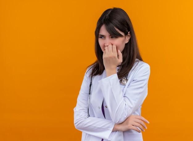 Geërgerd jonge vrouwelijke arts in medische mantel met stethoscoop legt hand op haar kin op geïsoleerde oranje achtergrond met kopie ruimte