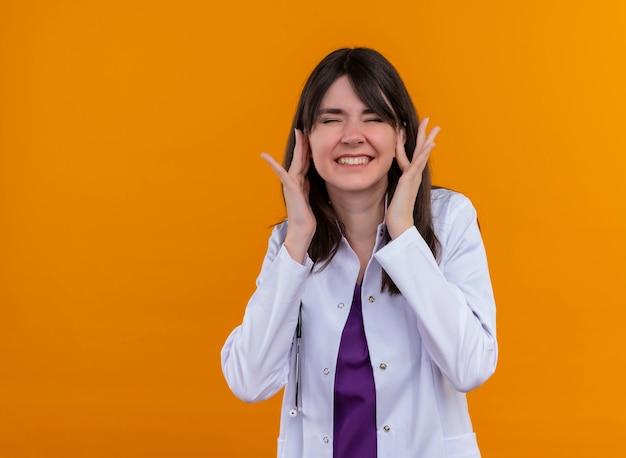 Geërgerd jonge vrouwelijke arts in medische mantel met stethoscoop sluit oren met vingers op geïsoleerde oranje achtergrond met kopie ruimte